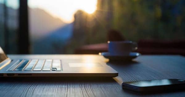 computer sitting on table during sunset